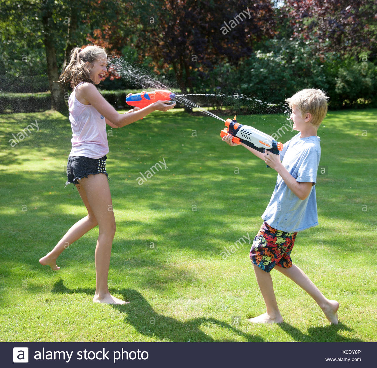 Brother and sister play fighting with water guns in garden - Stock Image