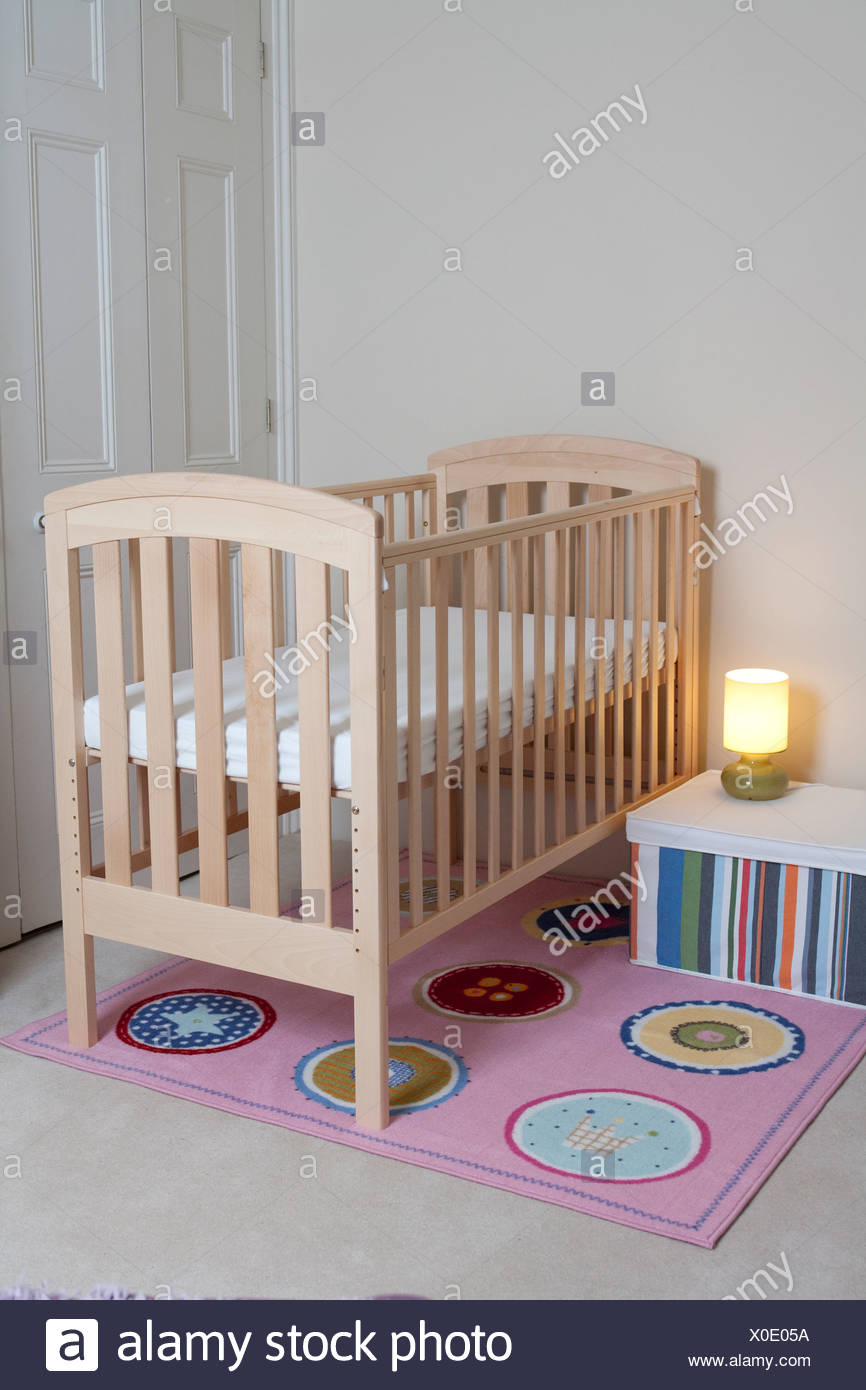 Baby's nursery with high sided cot and bed side light on - Stock Image