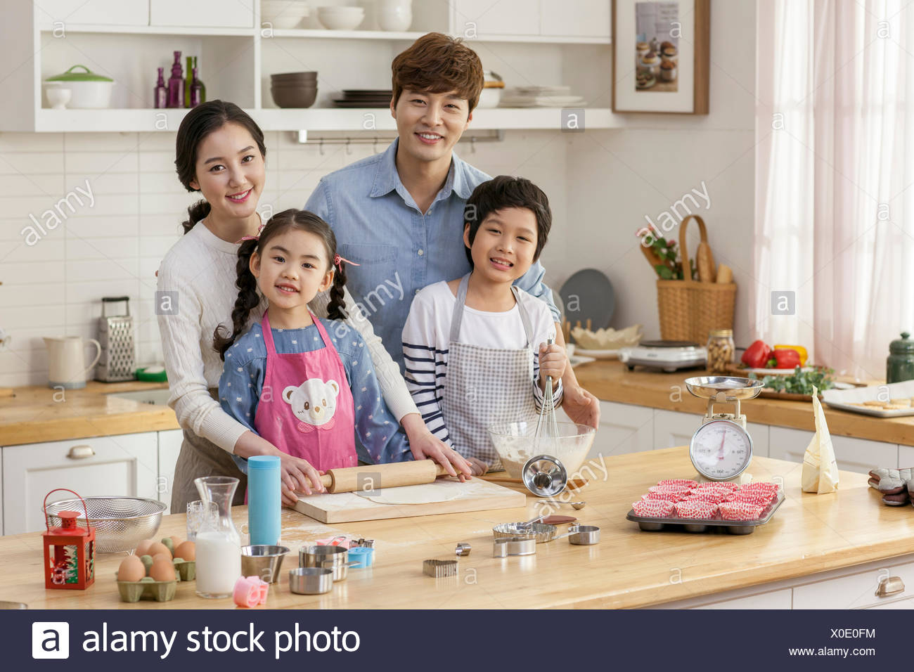 Harmonious family cooking together in kitchen - Stock Image