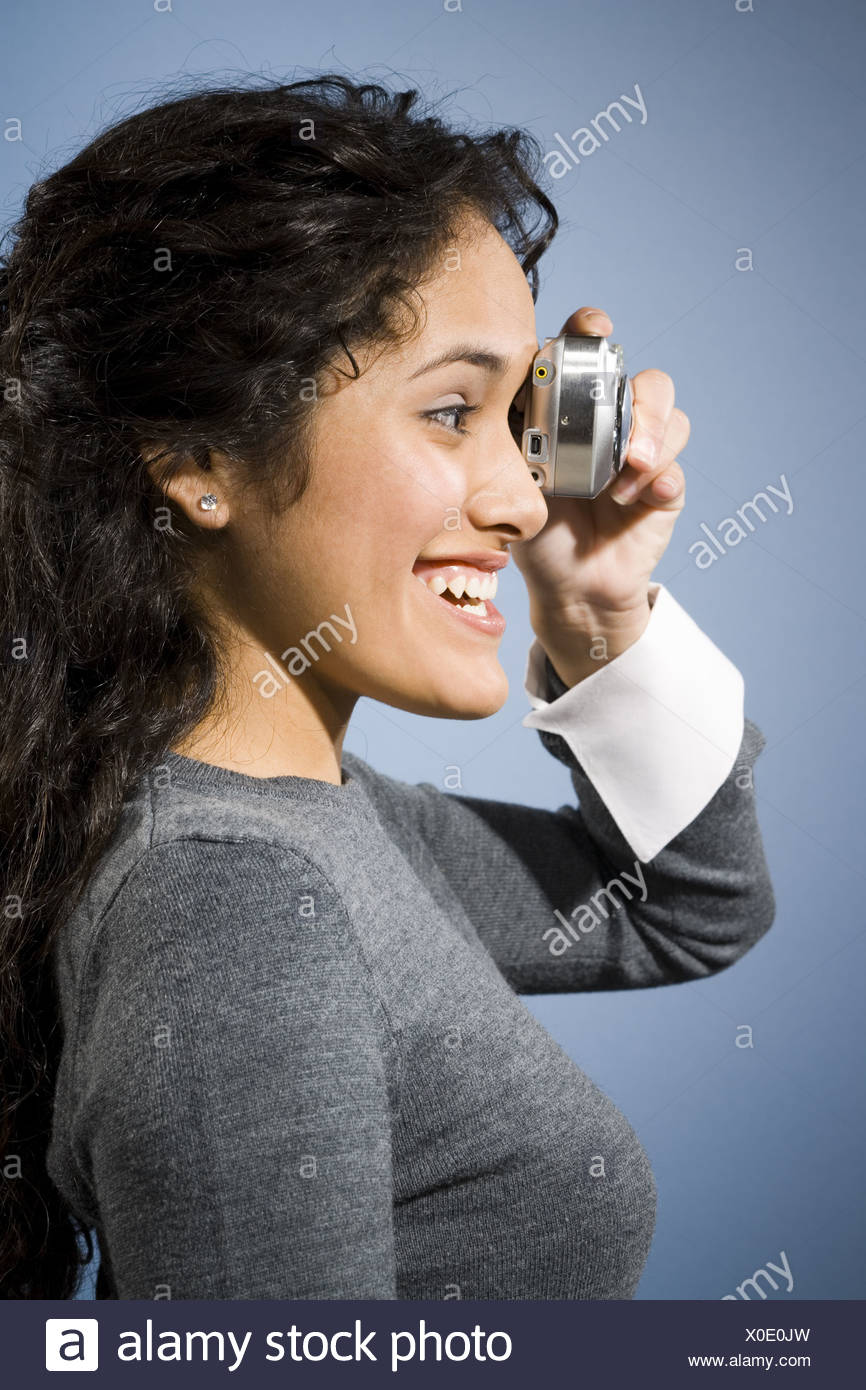 Profile of woman taking a photo with digital camera smiling - Stock Image