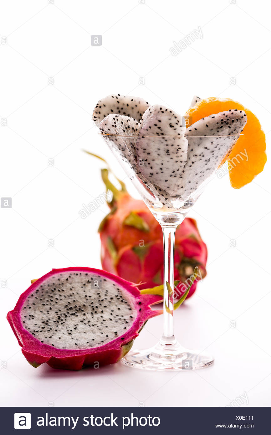 Pieces of pitaya pulp assorted in a cocktail glass and decorated with a mandarine slice. Next to it is a halved, and behind it, an entire Fruit. - Stock Image