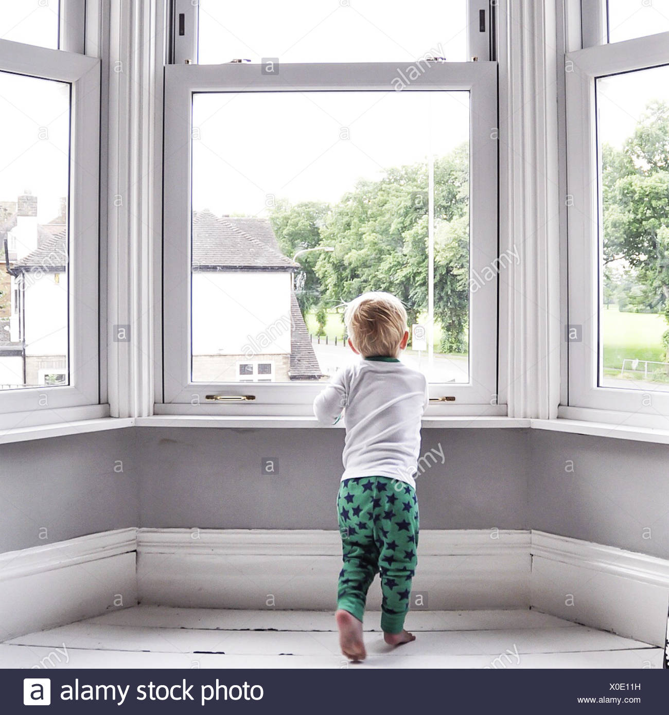 Boy looking out of living room window - Stock Image