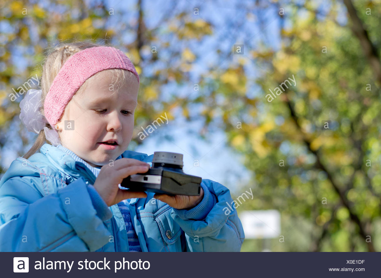 Small girl intrigued by an old camera - Stock Image