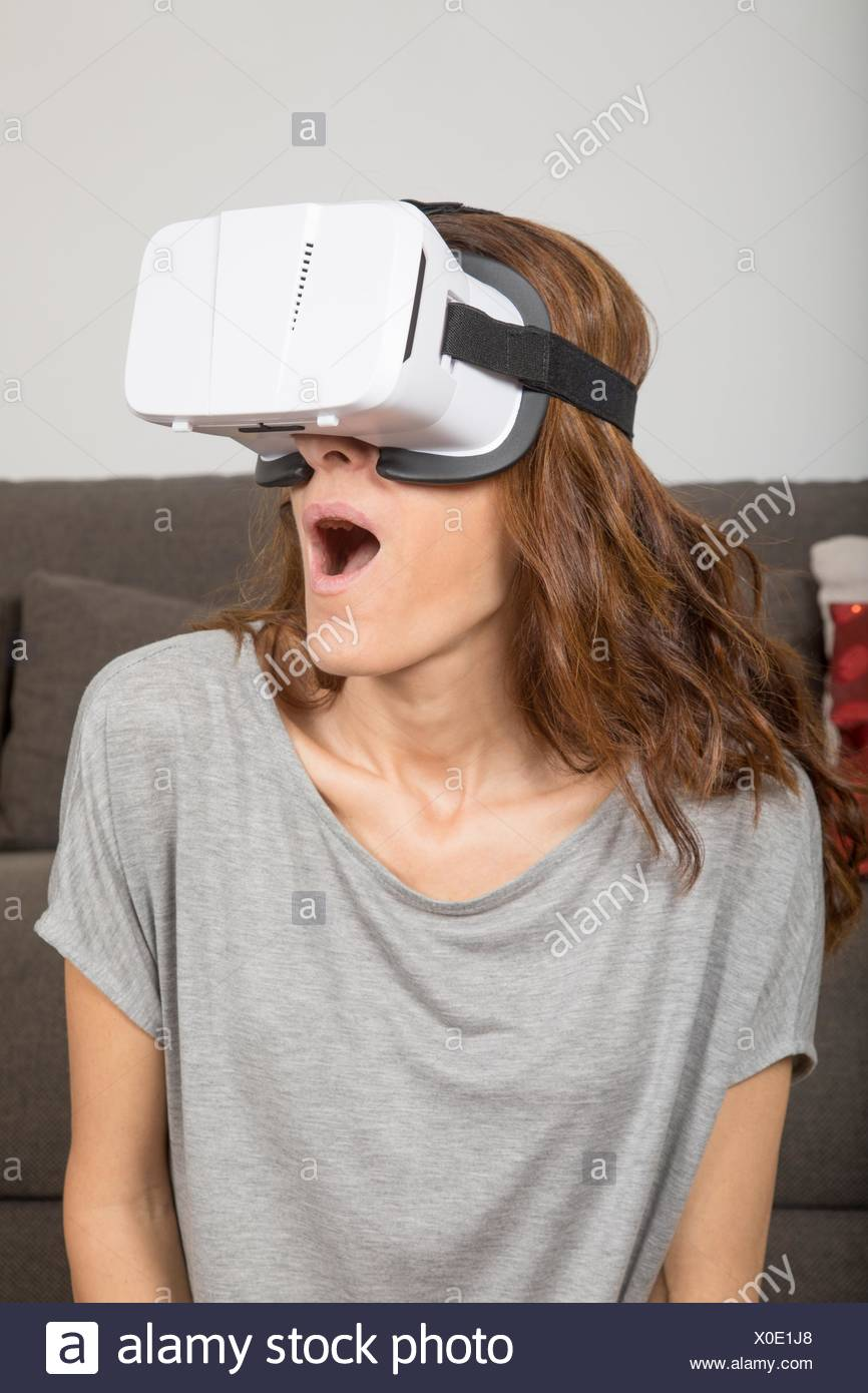 brown hair adult woman with virtual reality headset, or 360 glasses, grey  shirt, open mouth astonished face expression, indoor home.