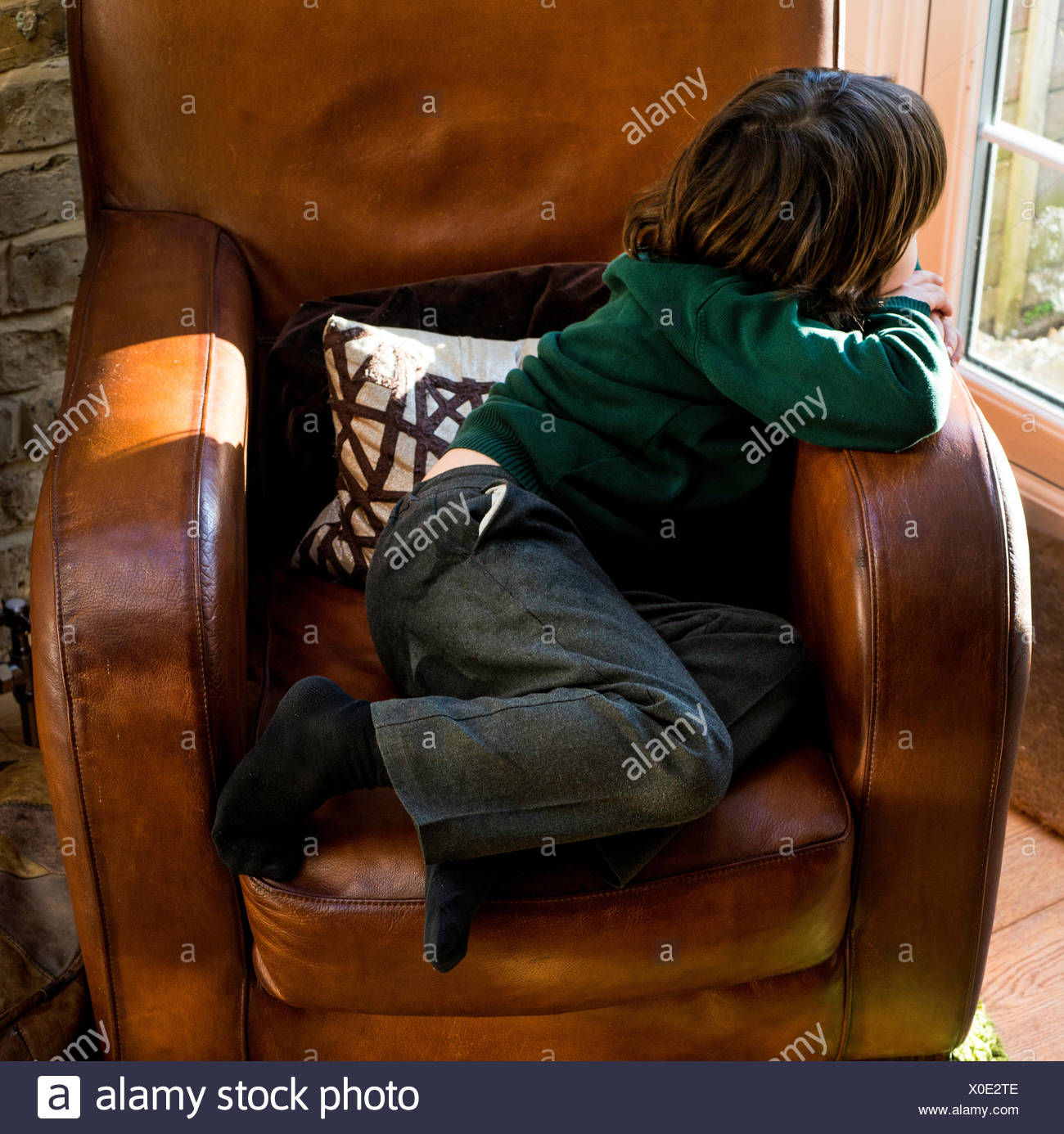 Boy relaxing on arm chair after school - Stock Image