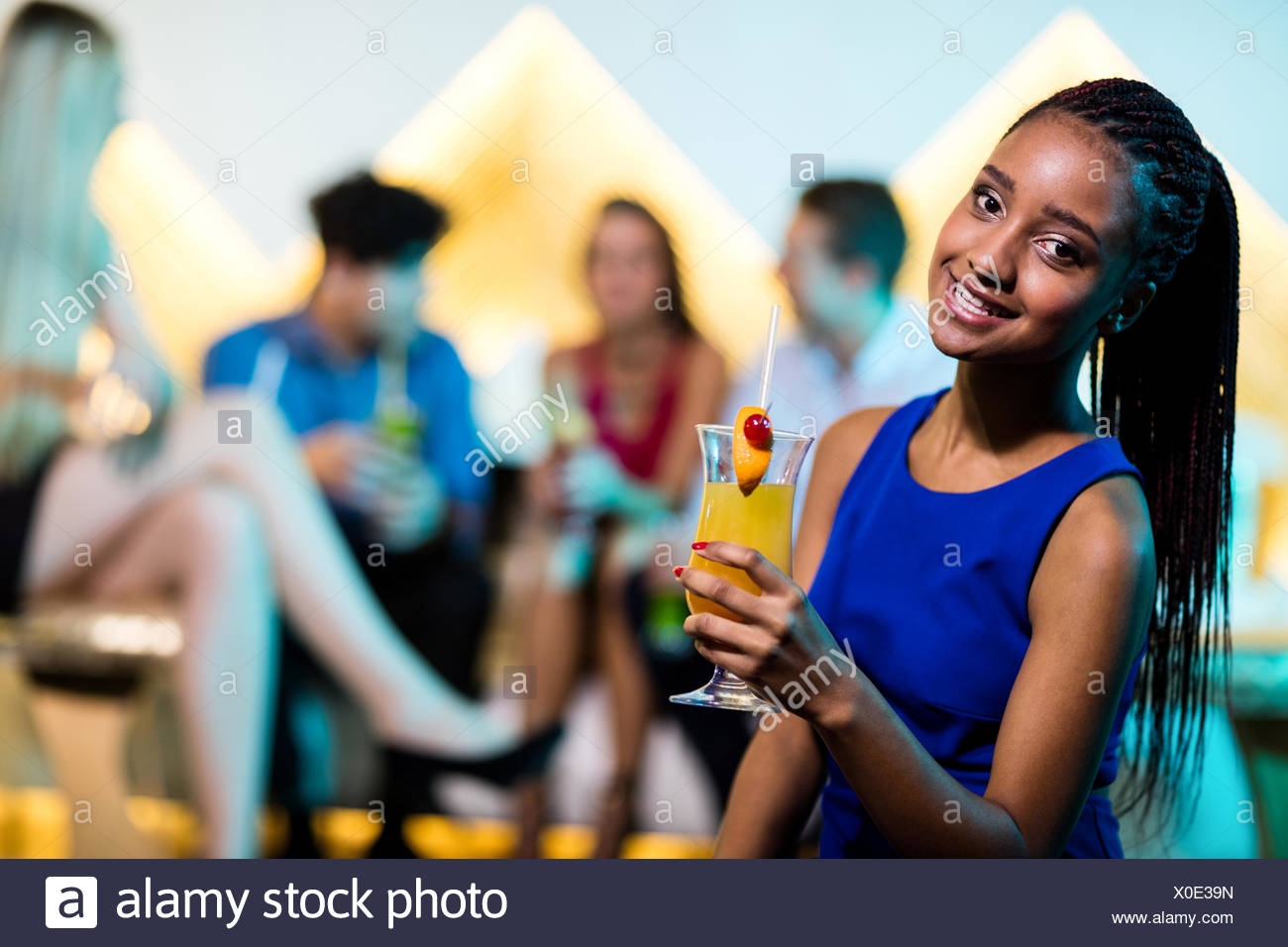 Portrait of beautiful woman having a cocktail - Stock Image