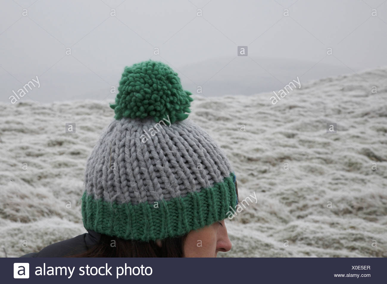 Young woman wearing woolly pom pom hat outdoors - Stock Image