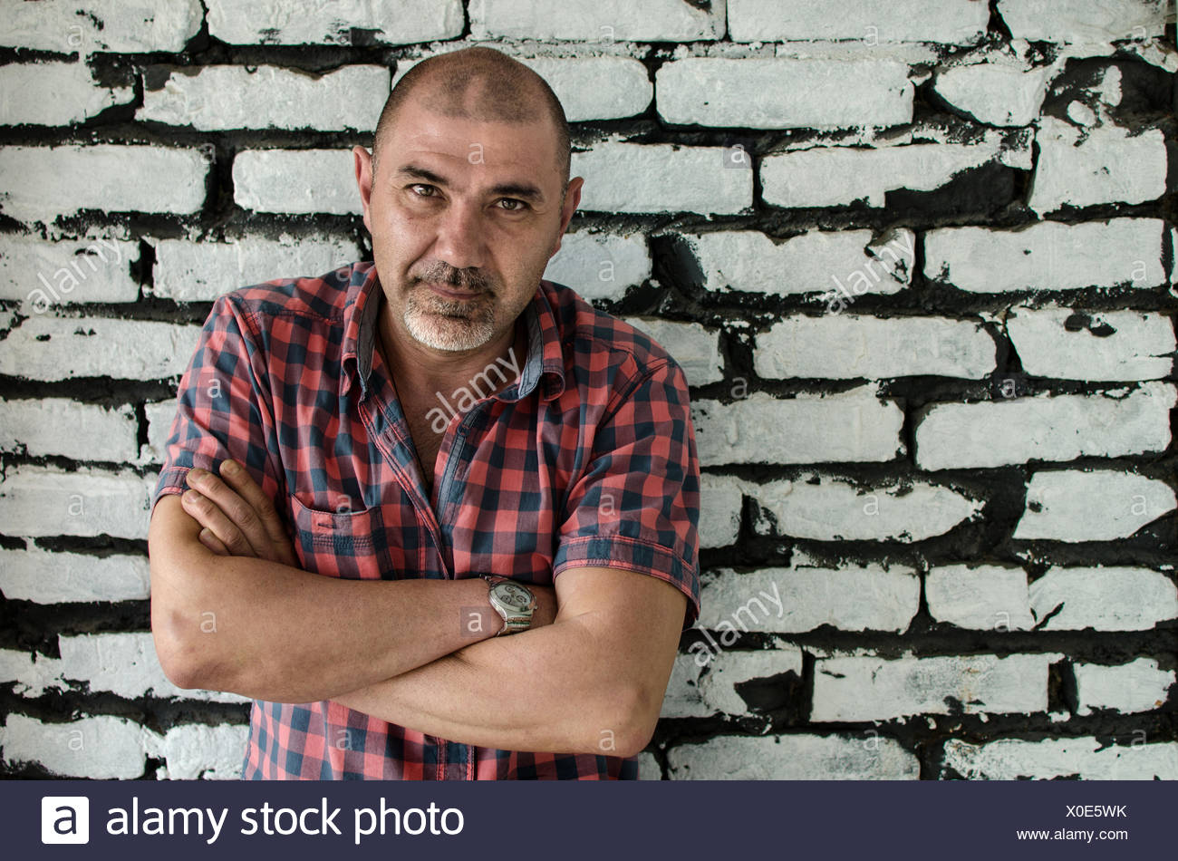 Portrait of a man with arms crossed standing by a brick wall - Stock Image