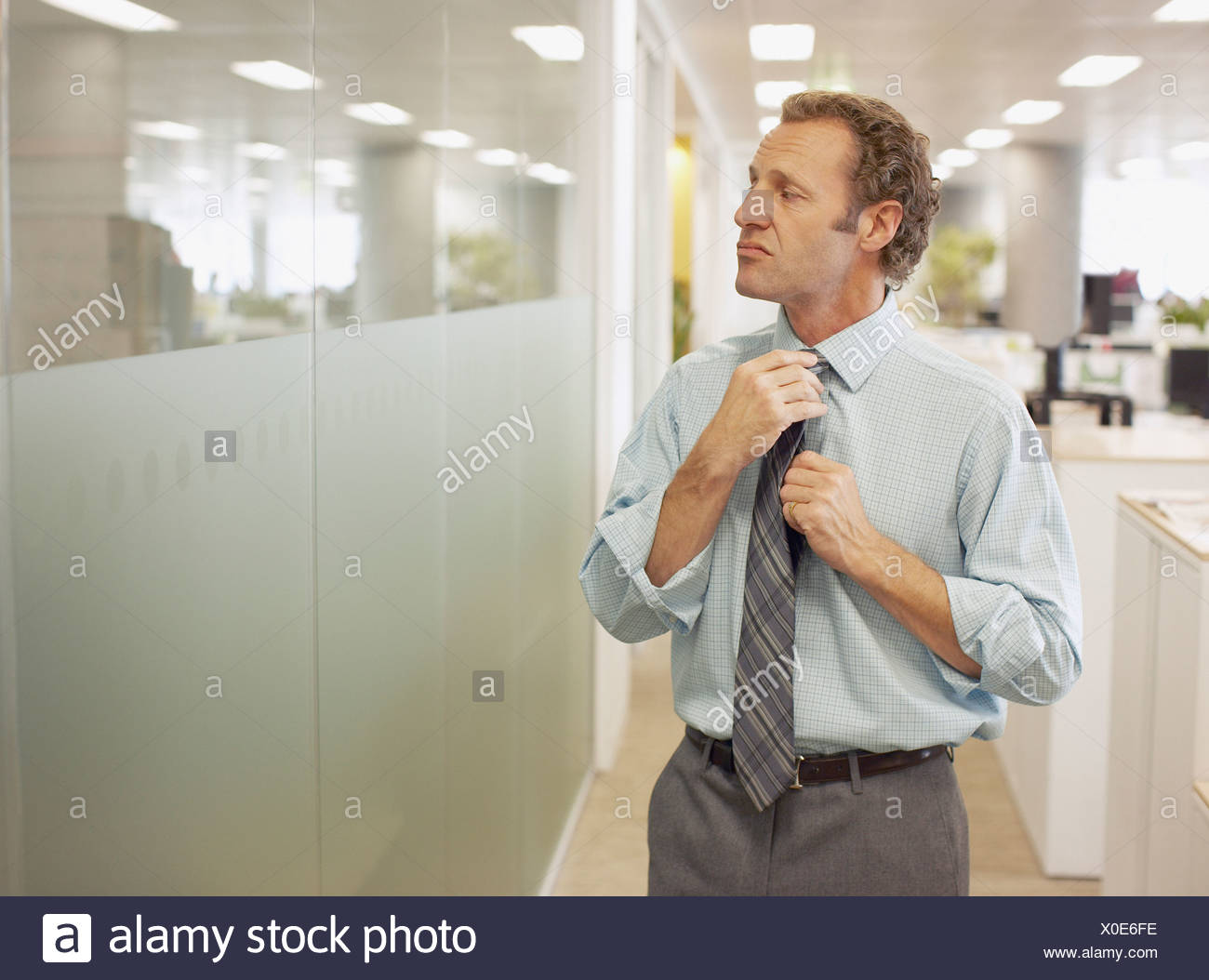 Businessman adjusting tie in office - Stock Image