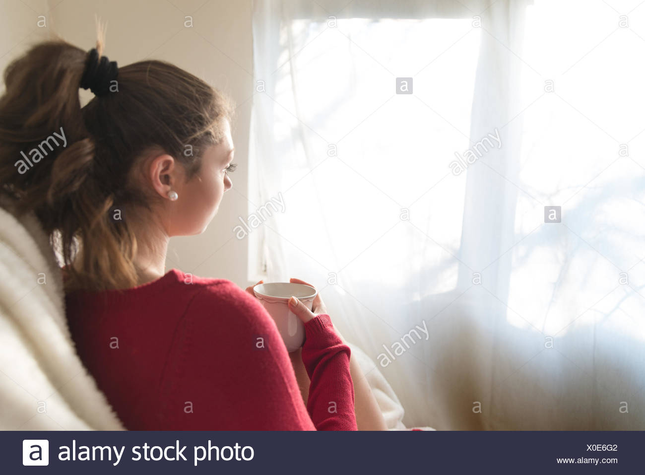 Girl with cup of tea looking through window - Stock Image