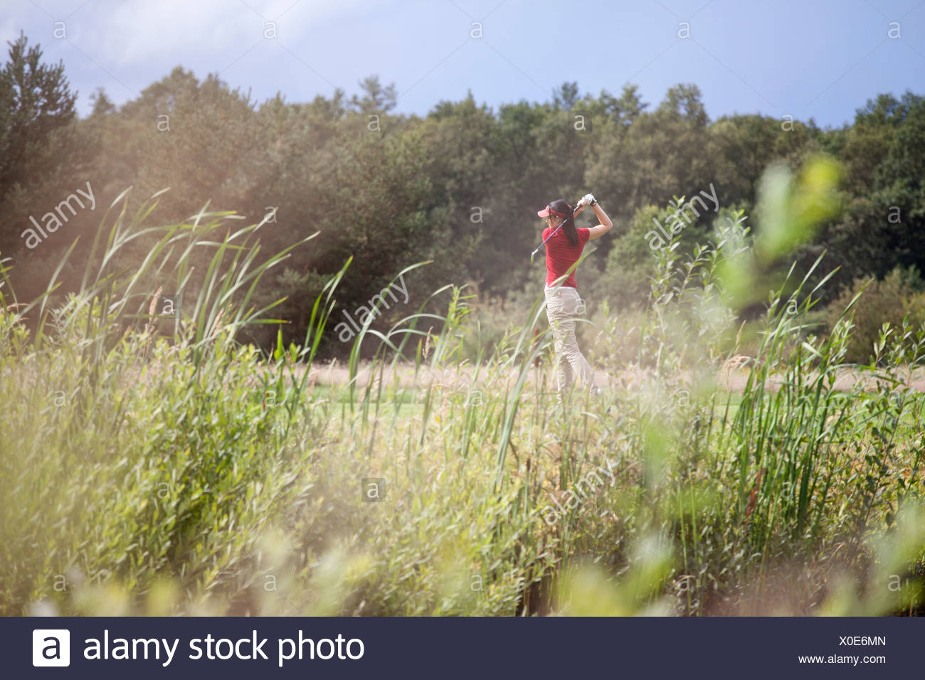 A female golfer teeing off - Stock Image