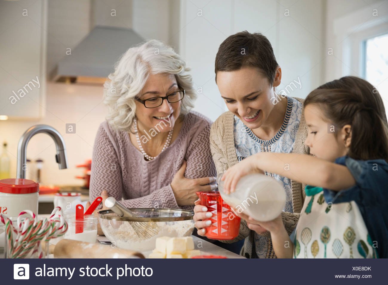 Three generation family baking cookies during Christmas - Stock Image