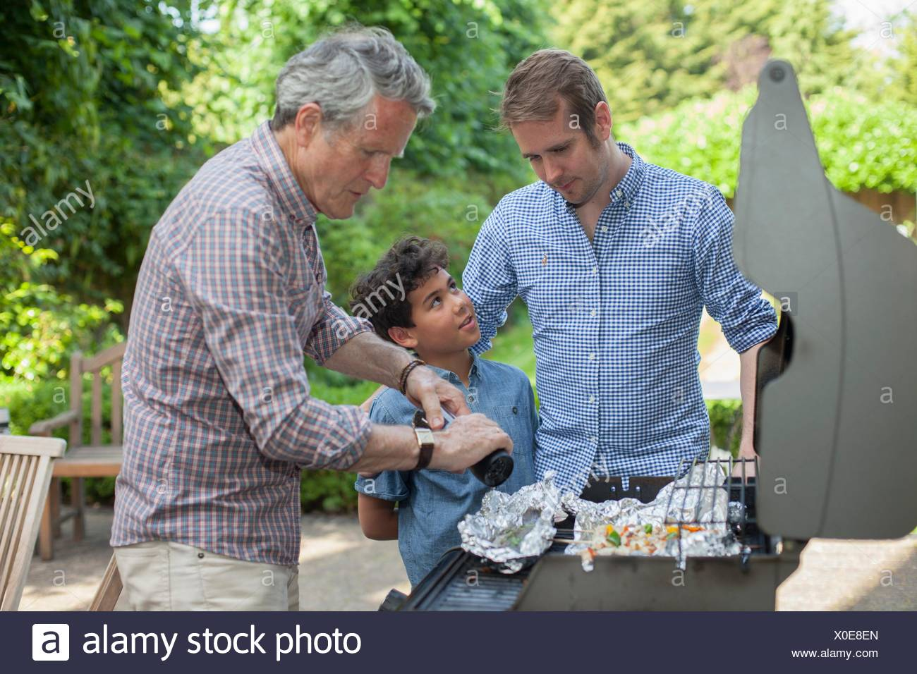 Three generation family cooking on barbecue - Stock Image