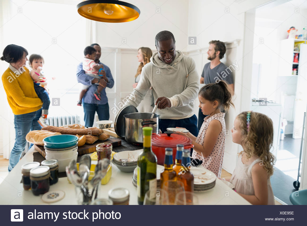 Families gathering for lunch in kitchen - Stock Image