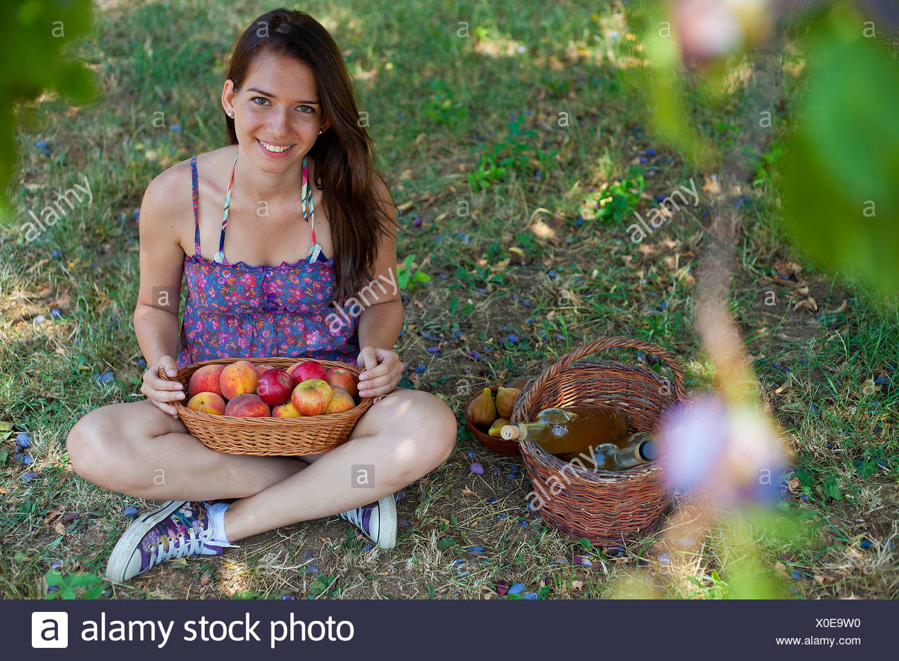 Smiling woman picnicking in orchard - Stock Image