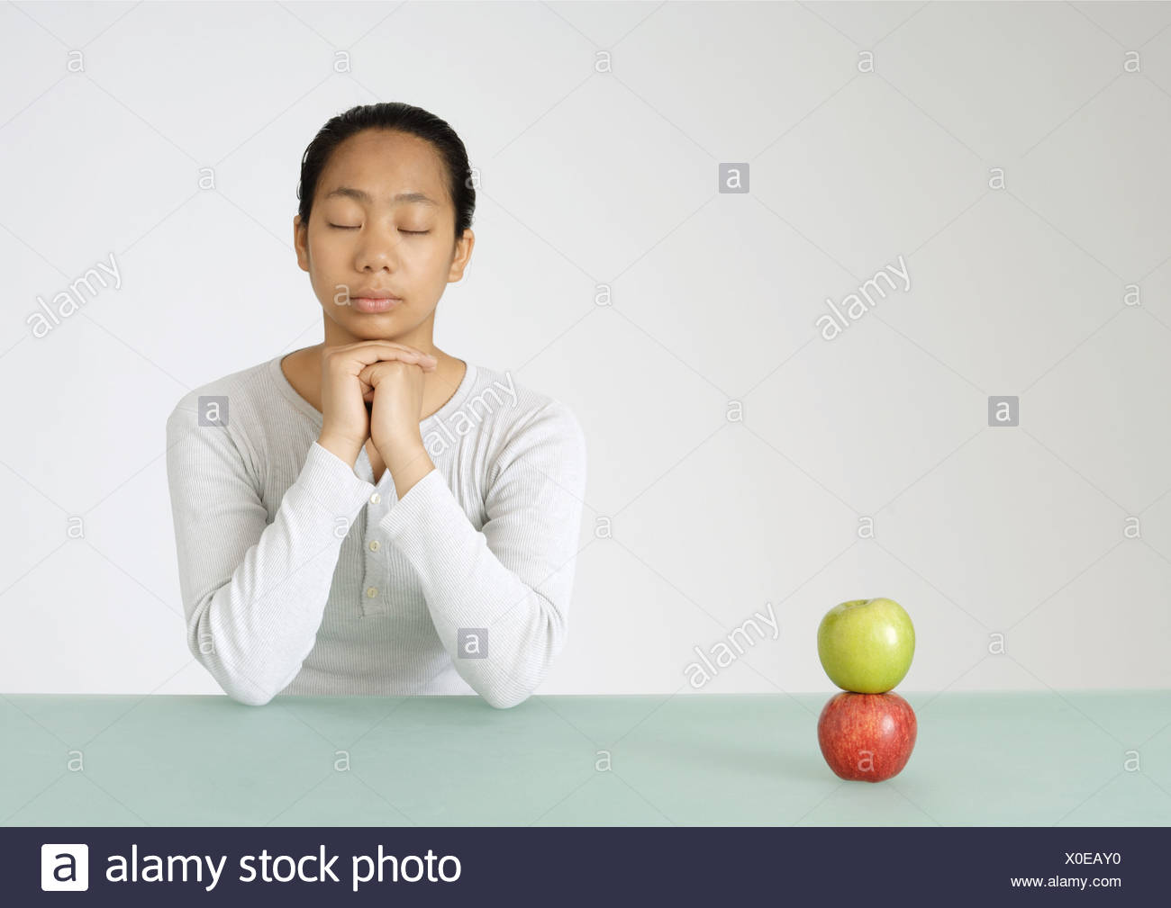 Young woman sitting with eyes shut, two apples stacked in front of her - Stock Image