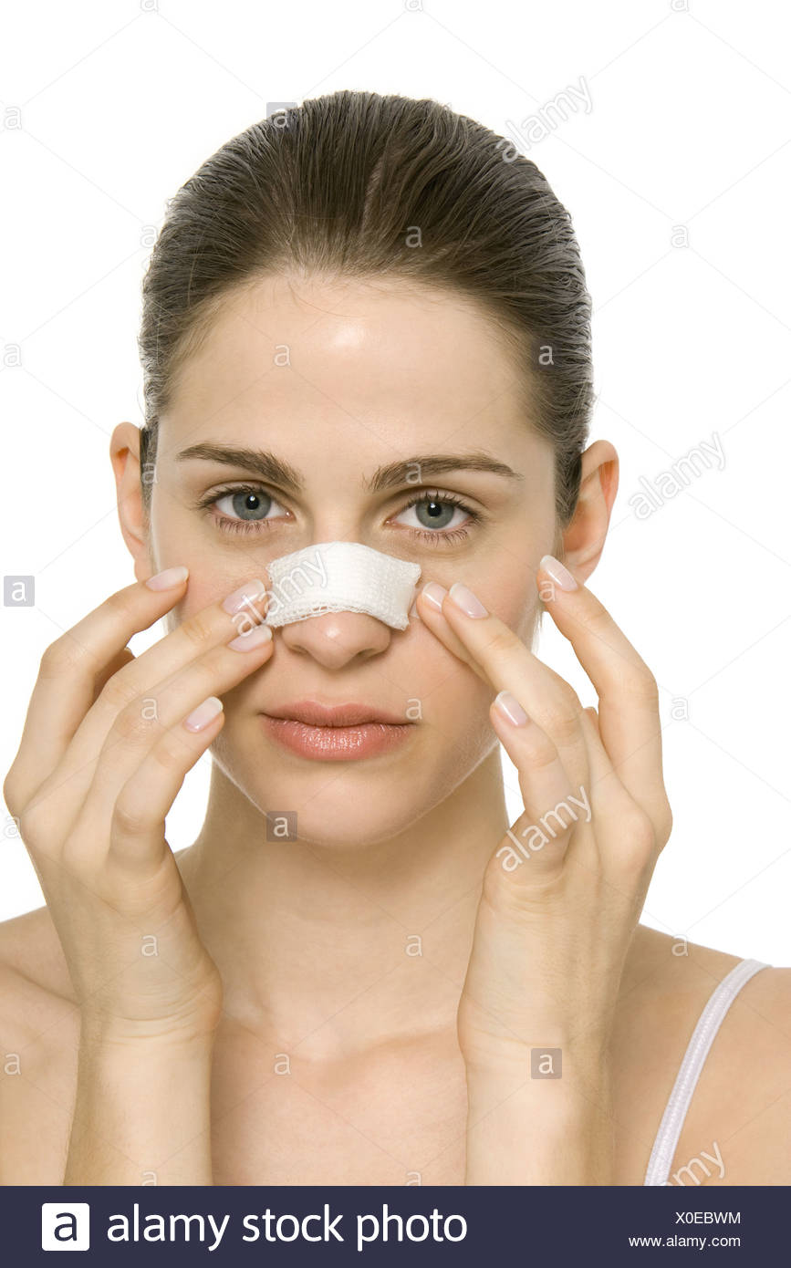Young woman with bandaged nose, touching face, portrait - Stock Image