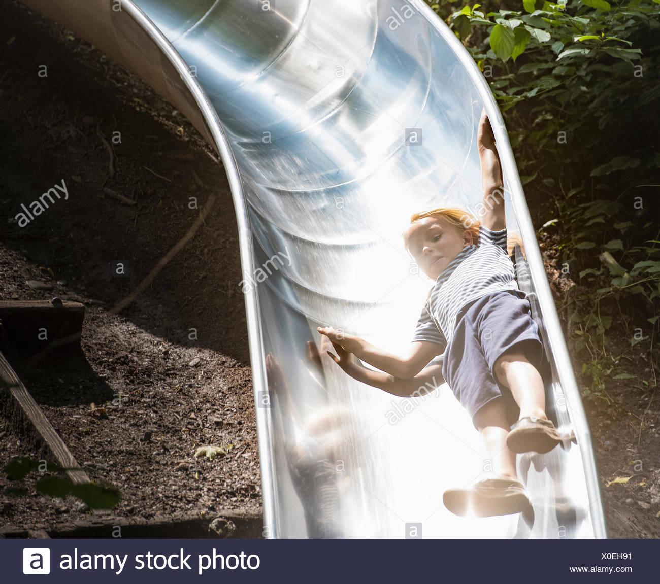 Boy sliding down playground slide - Stock Image