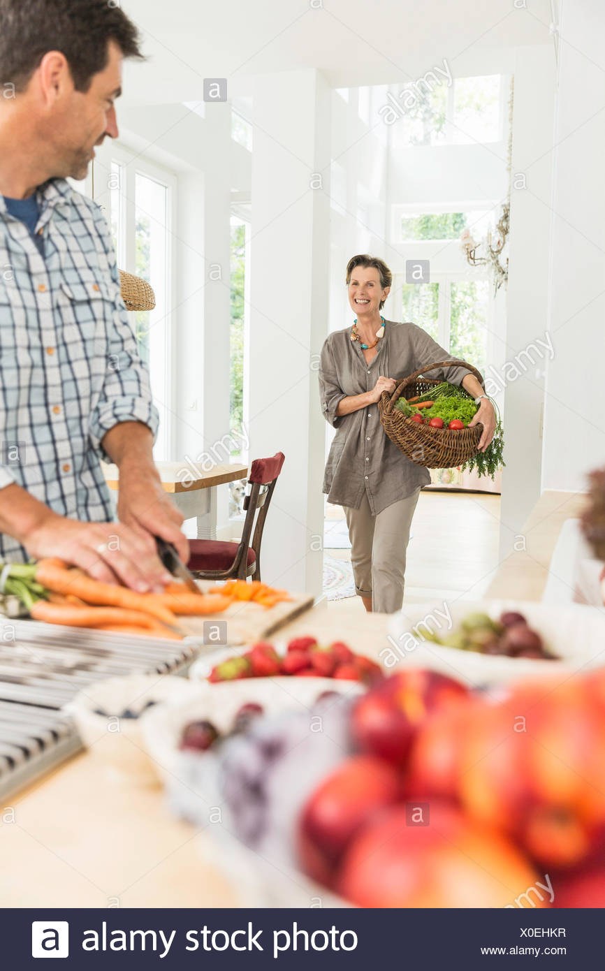 Couple carrying and preparing fresh vegetables in kitchen - Stock Image