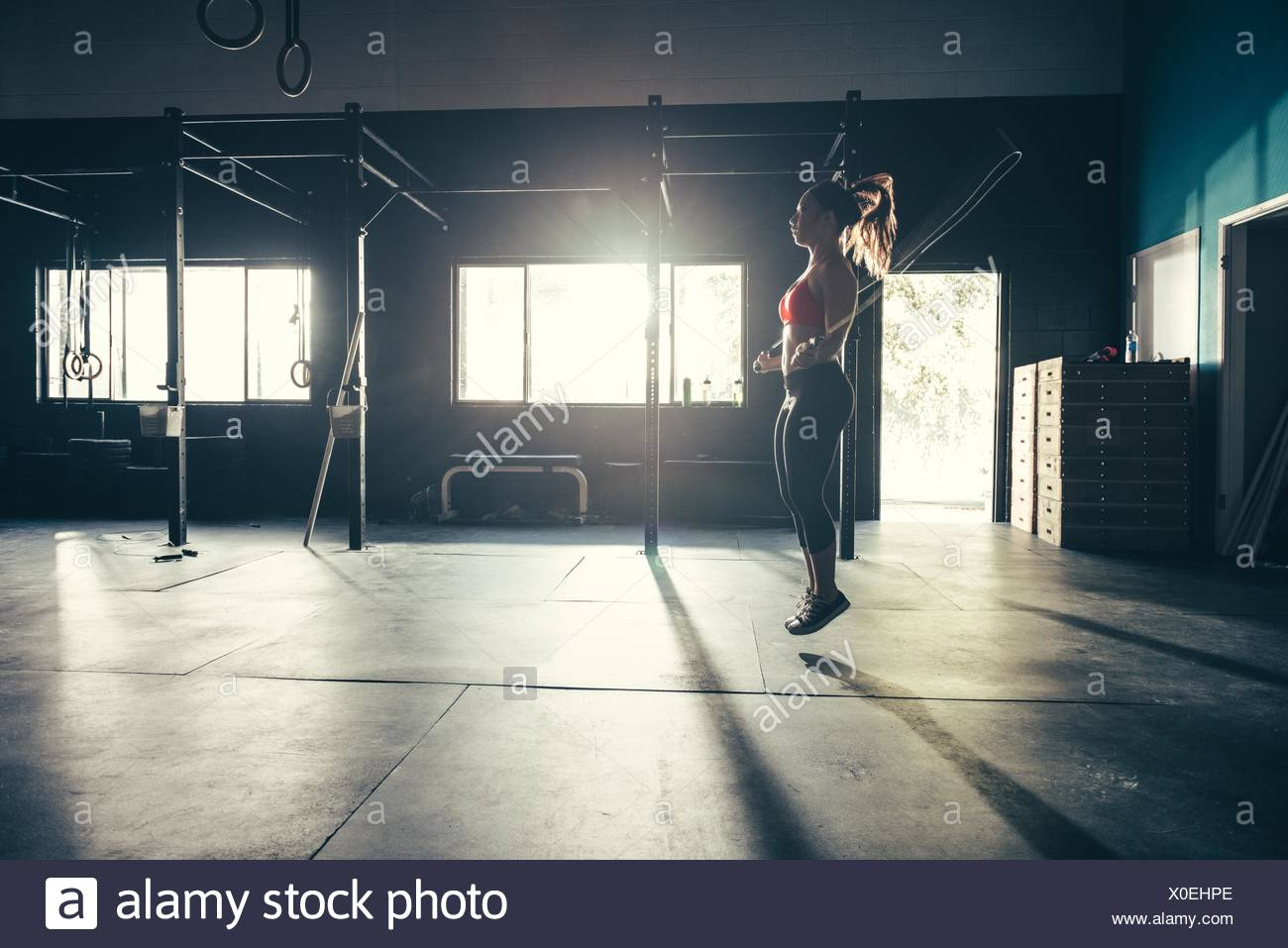 Woman skipping with skipping ropes in gym - Stock Image