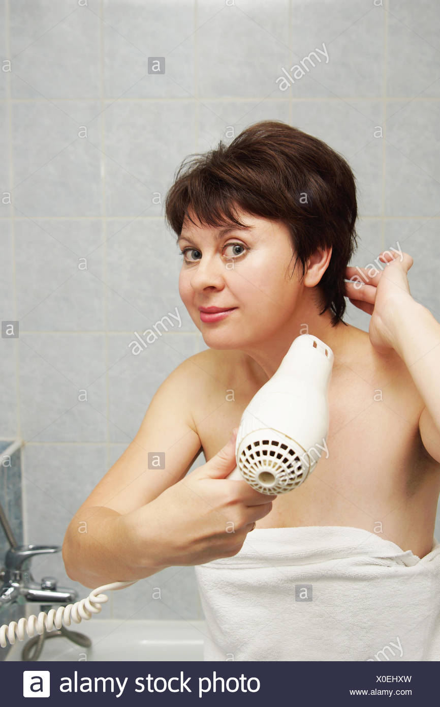 Nice Middle Aged Woman Dries Her Hair In A Bathroom Stock Photo