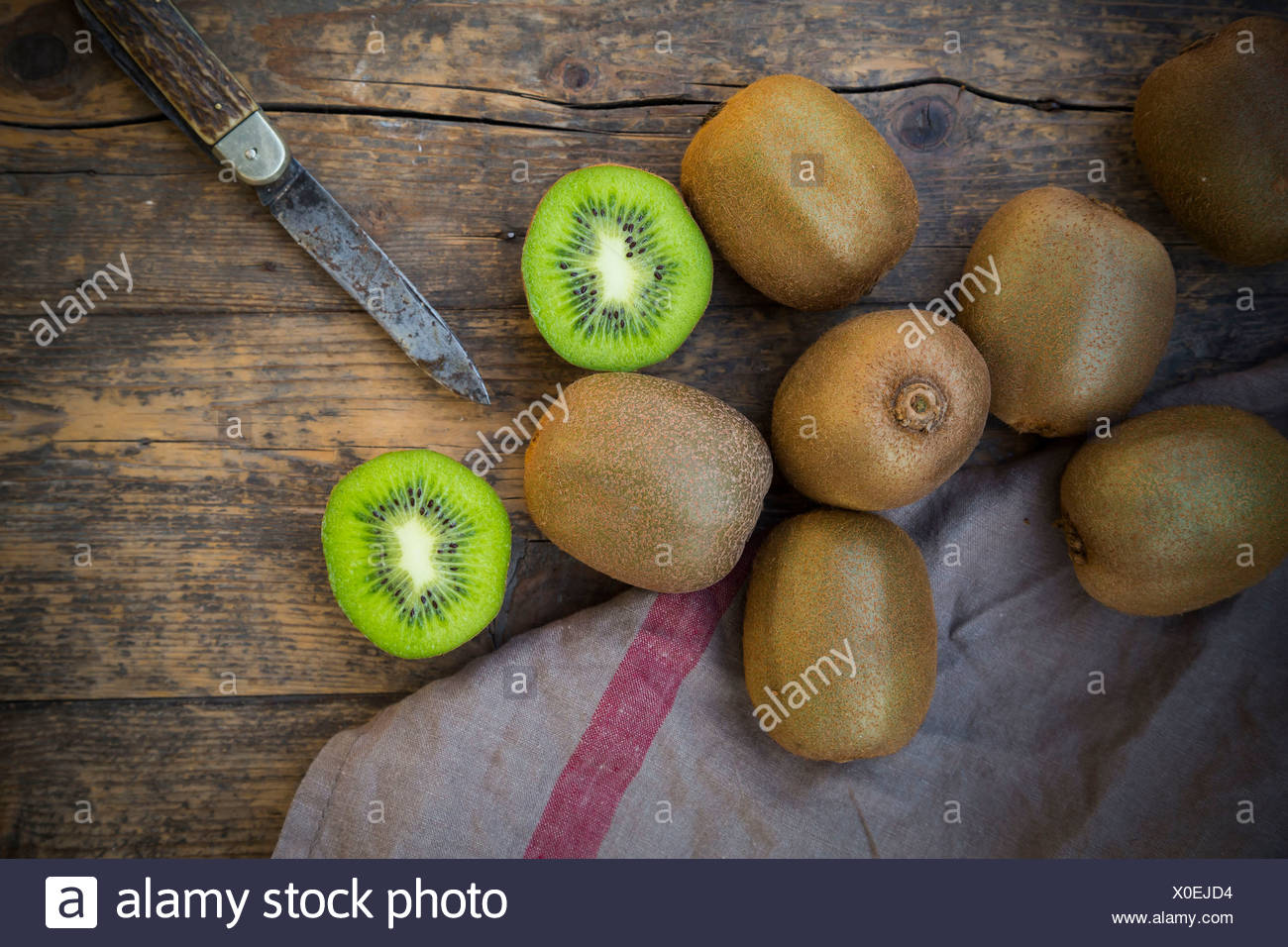 Kiwis (Actinidia deliciosa) and pocketknife on wooden table - Stock Image
