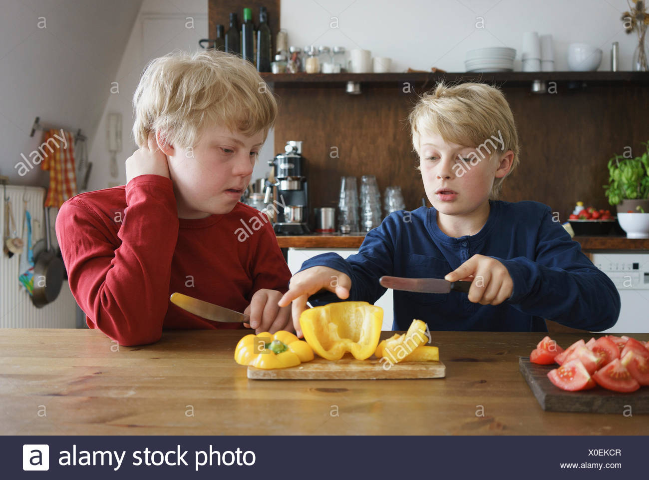Boy assisting brother to chop bell pepper at table in kitchen Stock
