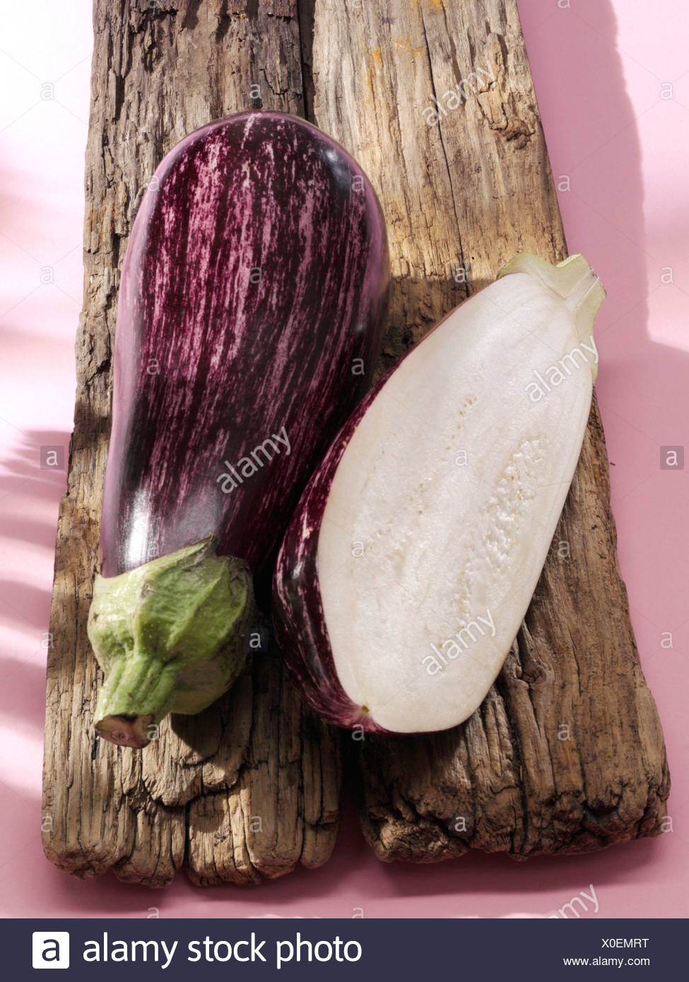 Two aubergines or eggplants (Solanum tuberosum) on a wooden board Stock Photo