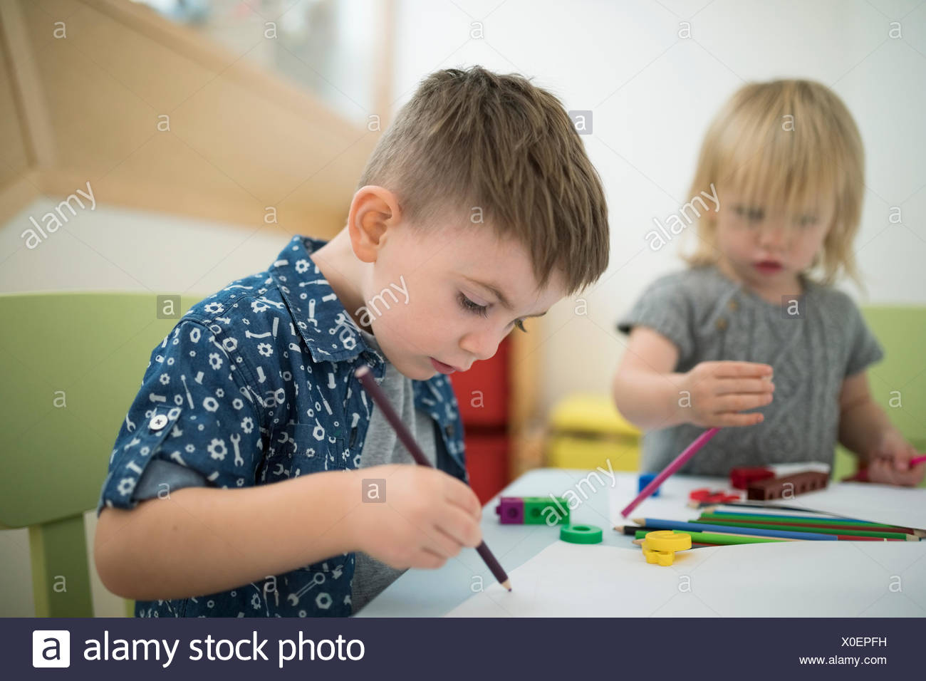 Toddler brother and sister drawing with colored pencils - Stock Image