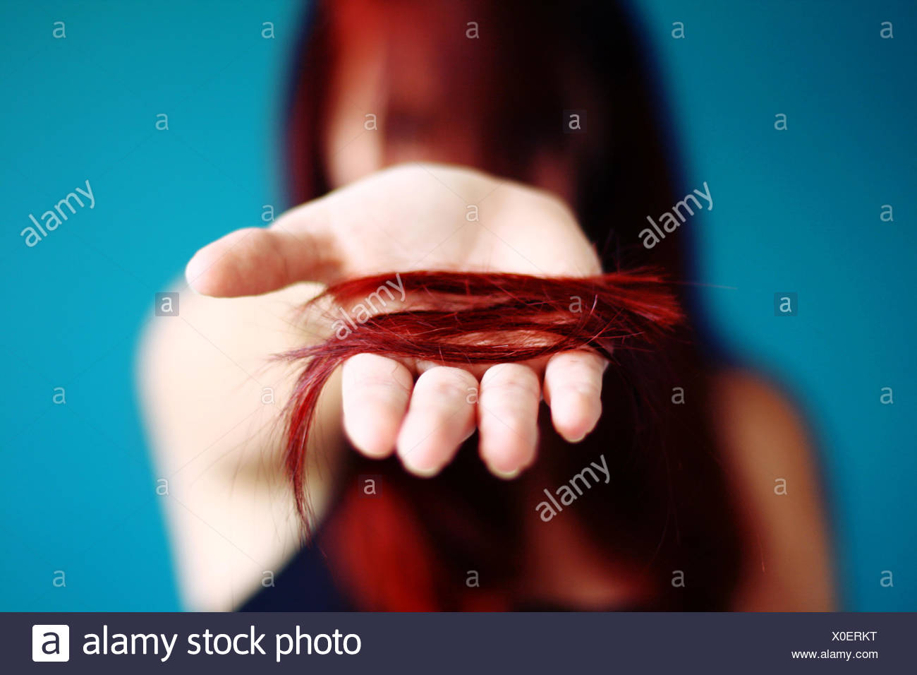 Young woman holding cut off hair - Stock Image