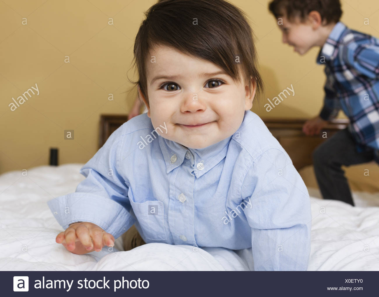 Two children playing on a bed  Pennsylvania USA - Stock Image
