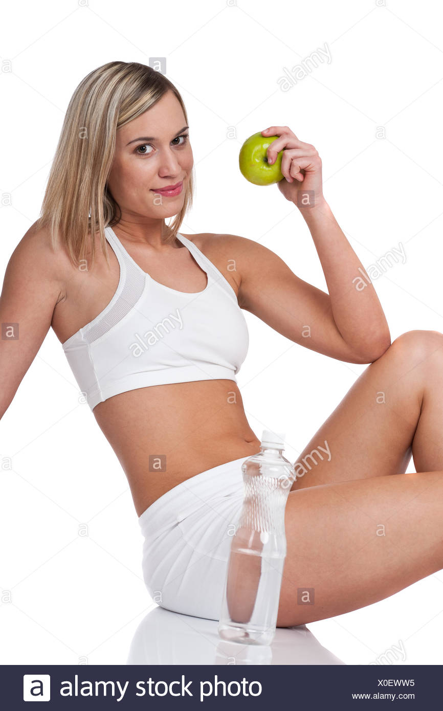 Fitness series - Blond woman in white outfit holding apple - Stock Image