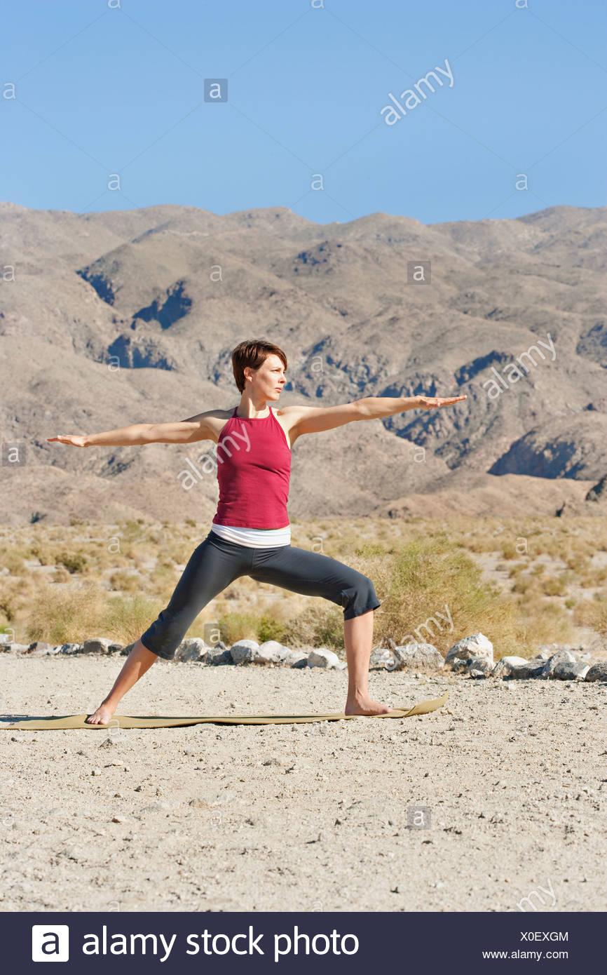 USA, California, La Quinta, Woman standing in yoga warrior pose in desert landscape - Stock Image
