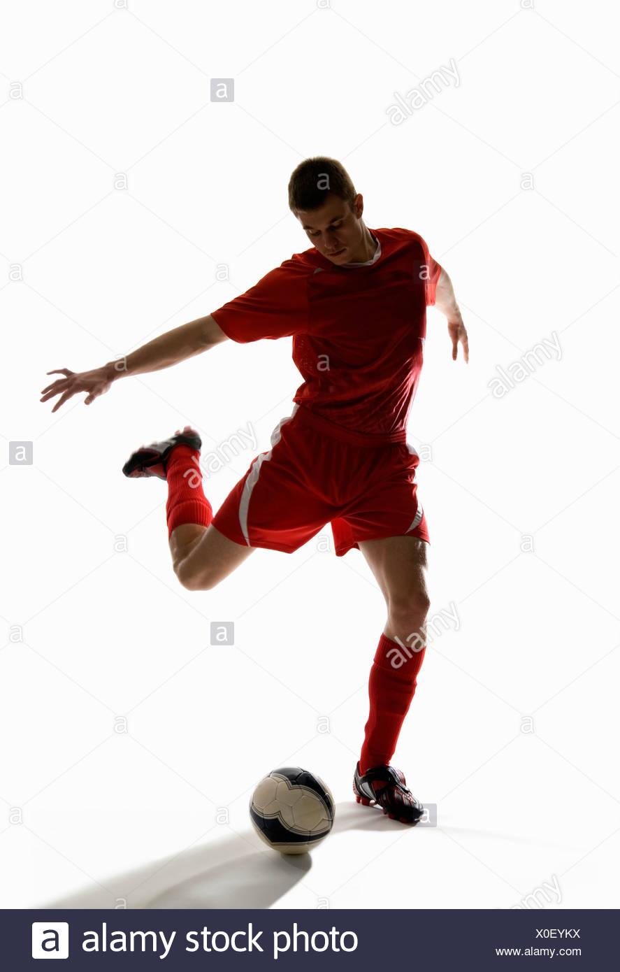 Studio shot of a soccer player kicking a soccer ball - Stock Image