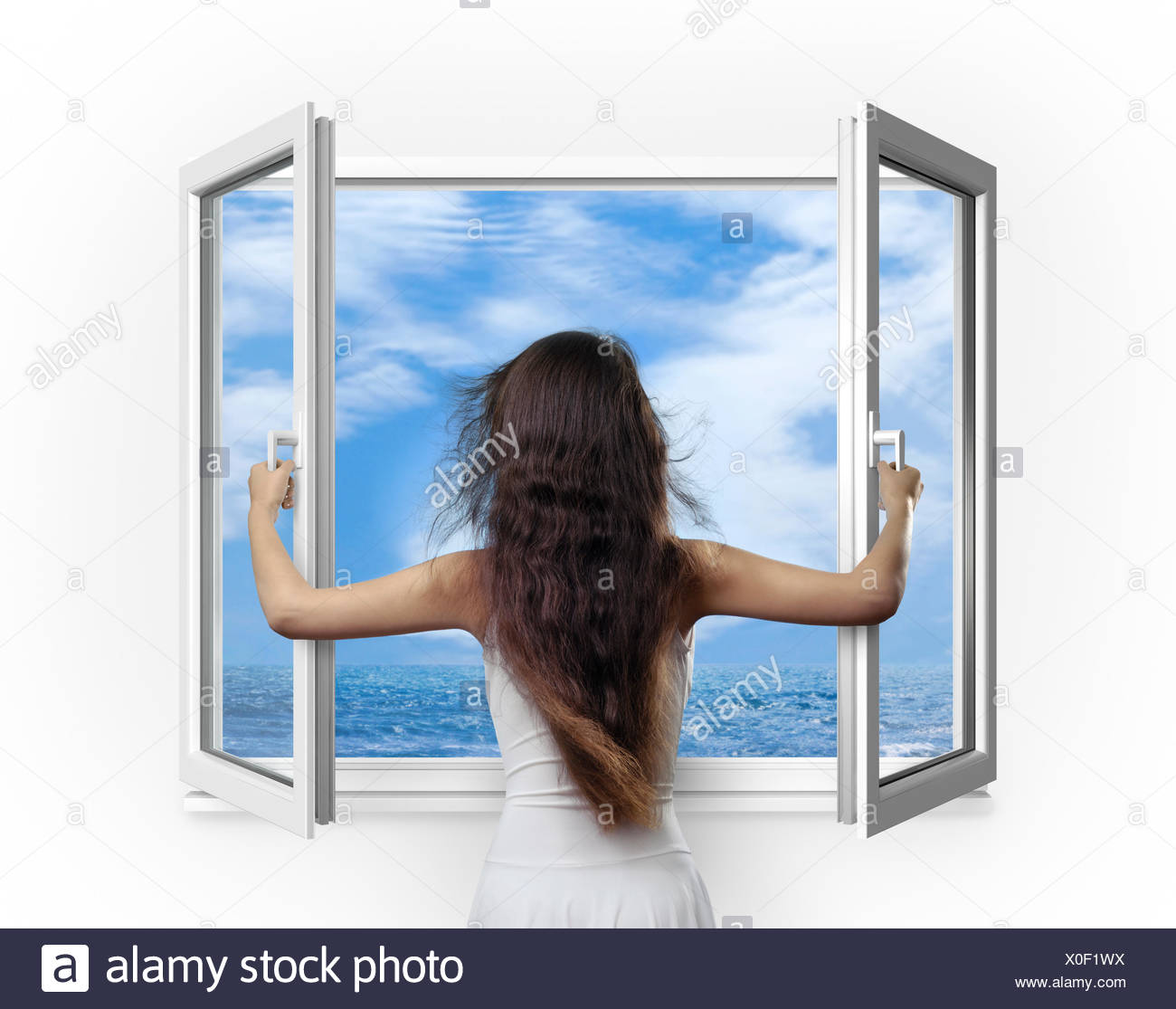 Young woman opening a window with a view onto the sea - Stock Image