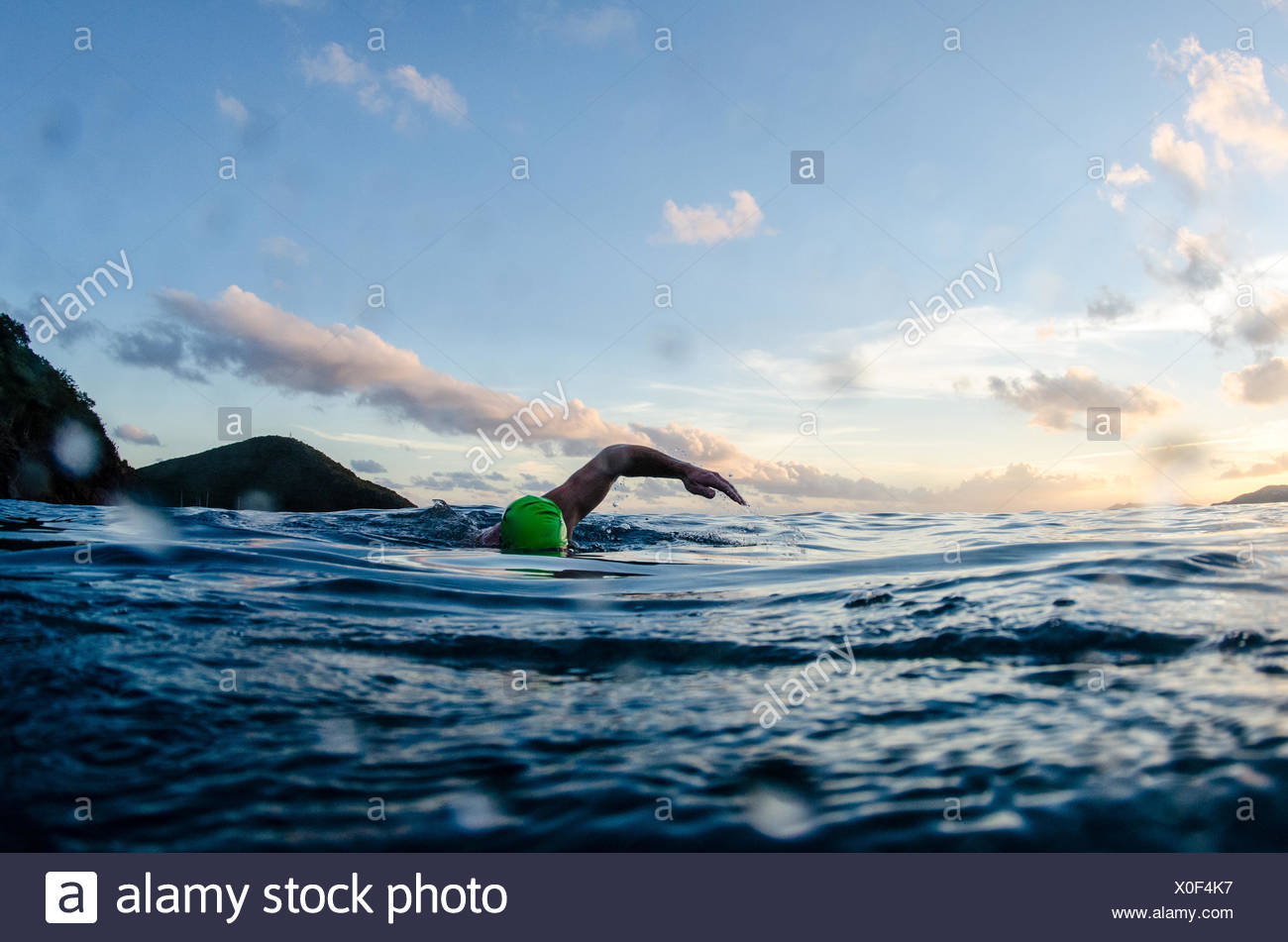 A man in a green swim cap swims at dusk, his arm is in mid stroke. - Stock Image