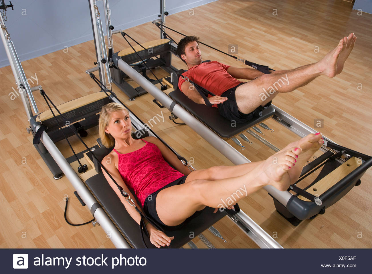 Young couple working out on Pilates exercise equipment in gym - Stock Image