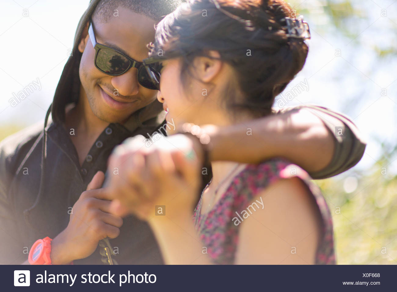 Close up of romantic young couple holding hands - Stock Image