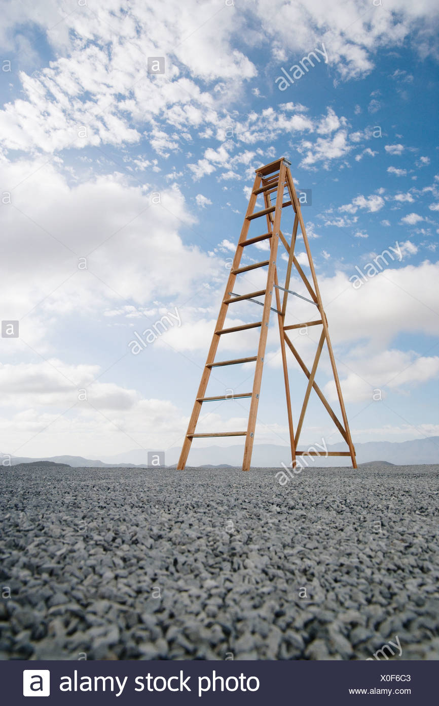 Ladder outdoors ground level view with blue sky and clouds - Stock Image