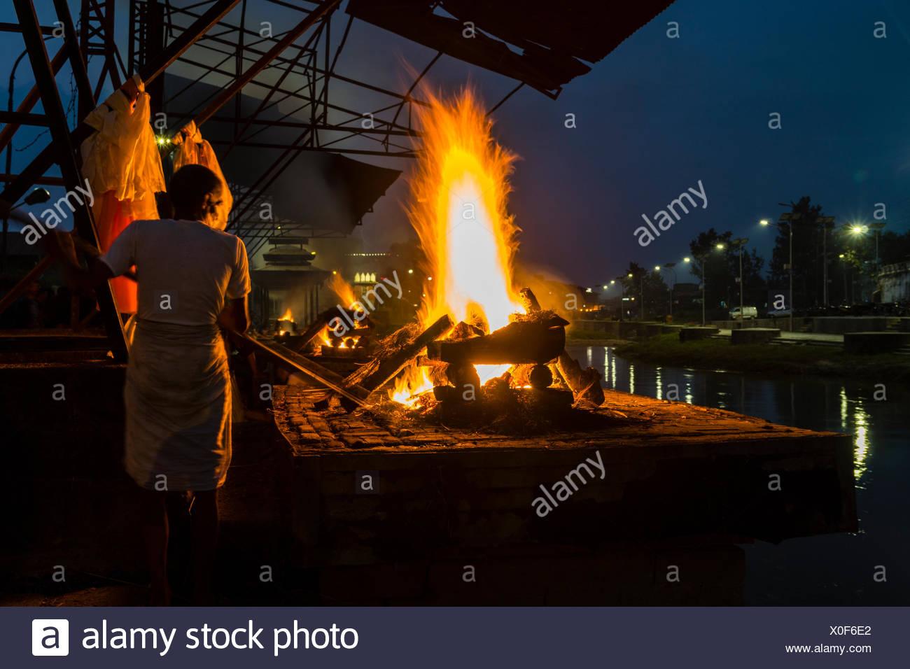 Cremation of a dead body at the burning ghats at night, Pashupatinath temple, banks of Bagmati River, Kathmandu - Stock Image