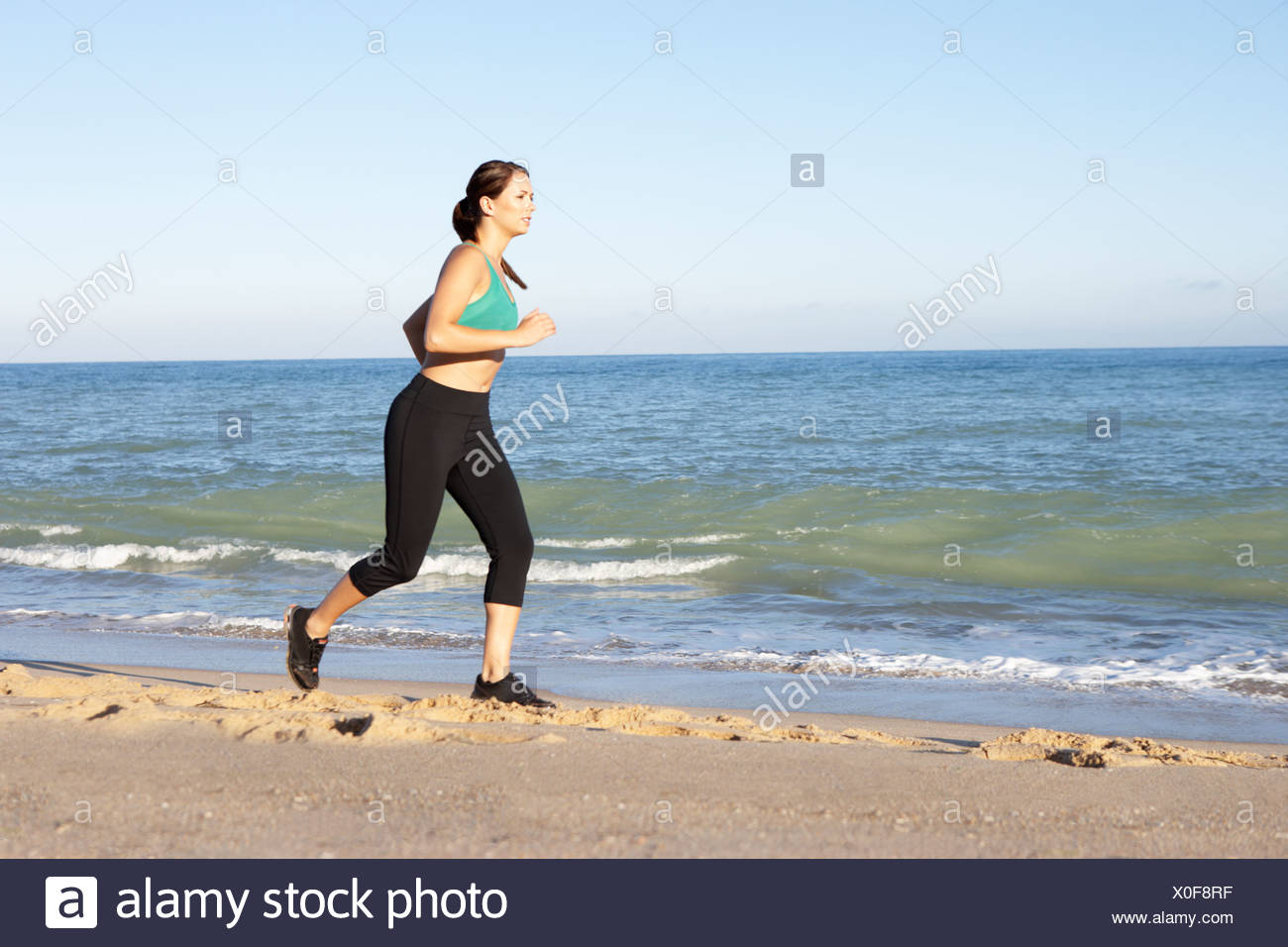 Young Woman Fitness Clothing Running Along Beach - Stock Image
