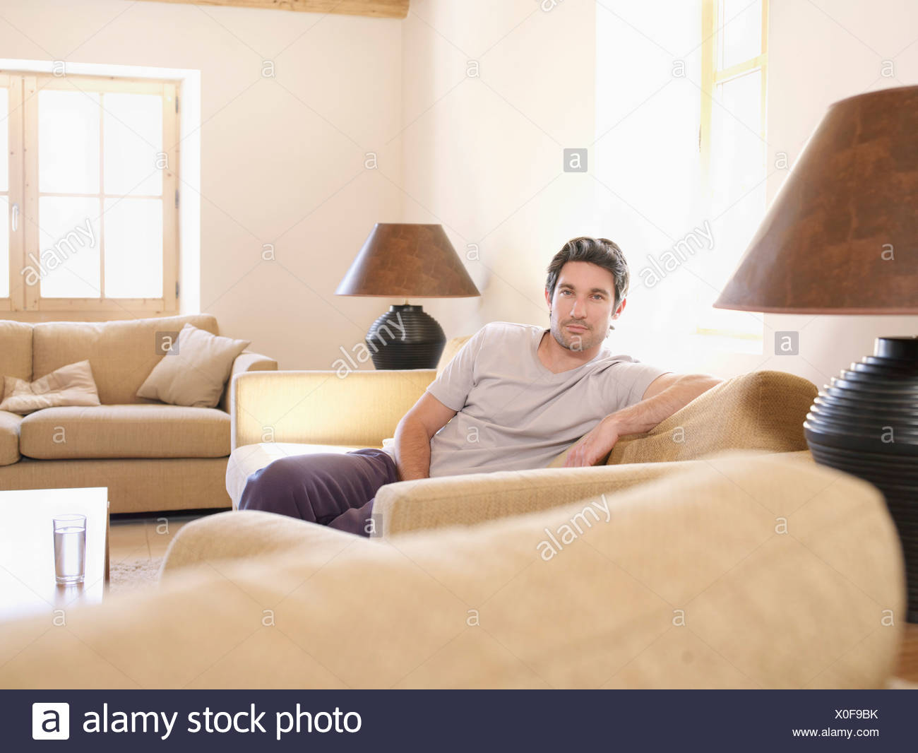 Man relaxing on sofa in living room - Stock Image