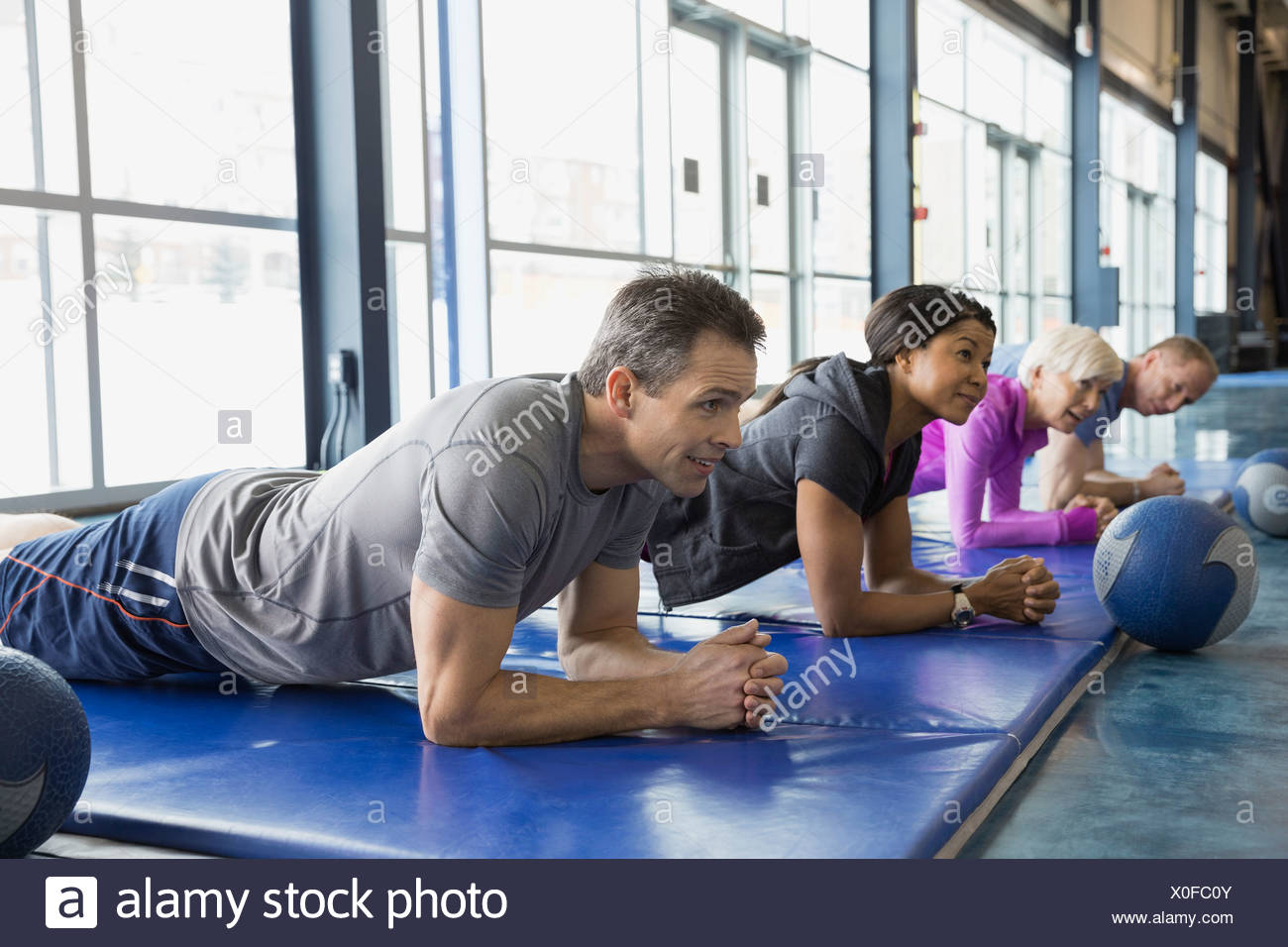 Group doing planks in exercise class at gym - Stock Image