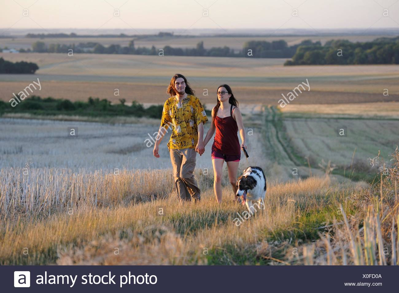 couple of young people walking with a dog around Mittainville, Yvelines department, Ile-de-France region, France, Europe. Stock Photo
