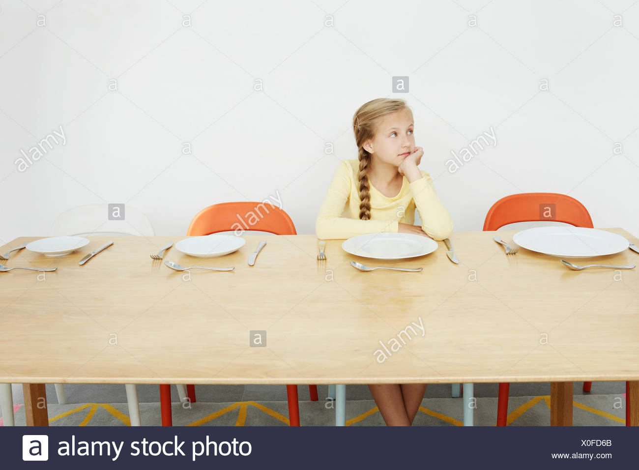 Girl sitting at table with empty plate, looking away - Stock Image