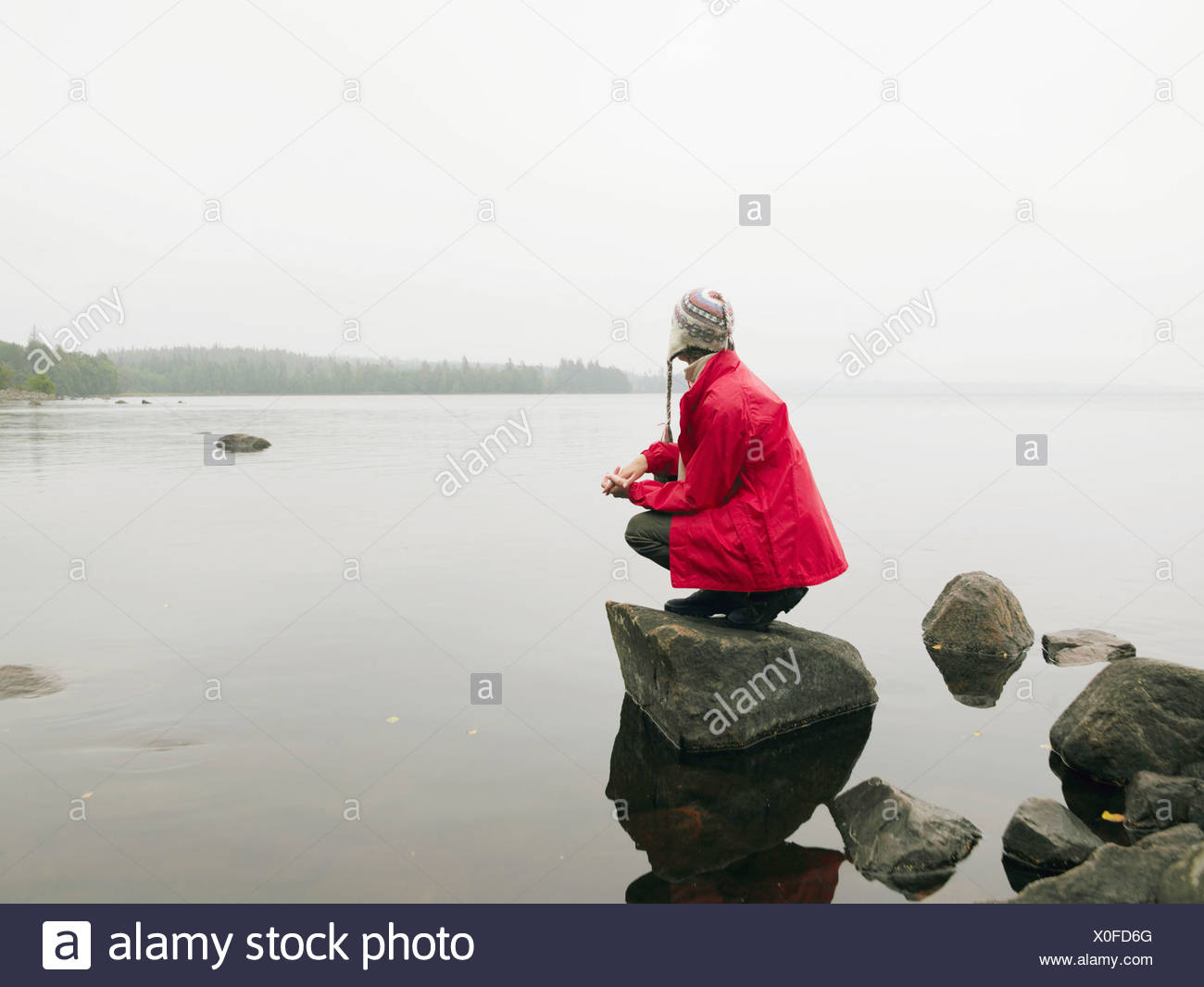 Woman crouching on large rock in the water. - Stock Image