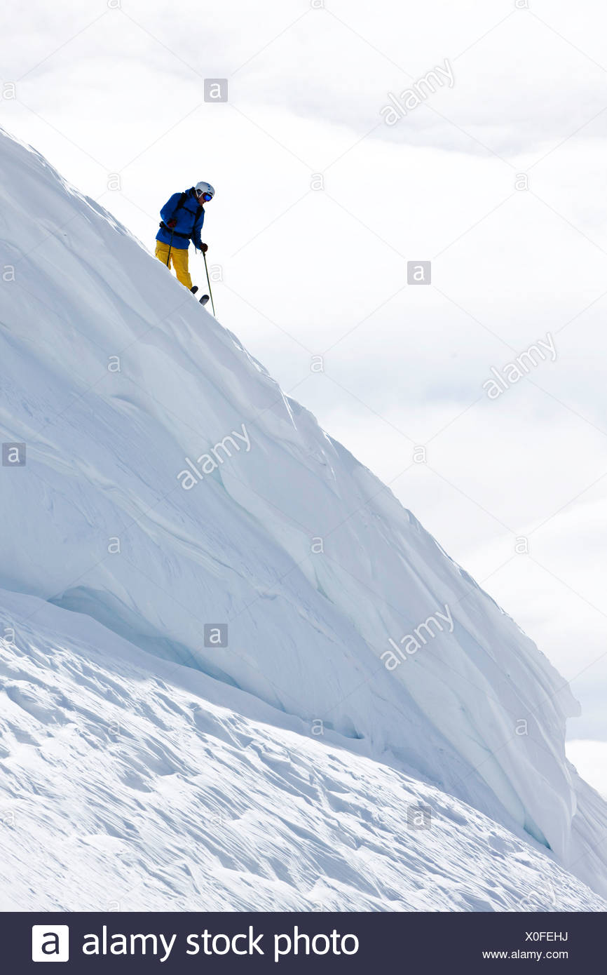 A skier scouts his line standing on top of a huge cornice in Colorado. - Stock Image