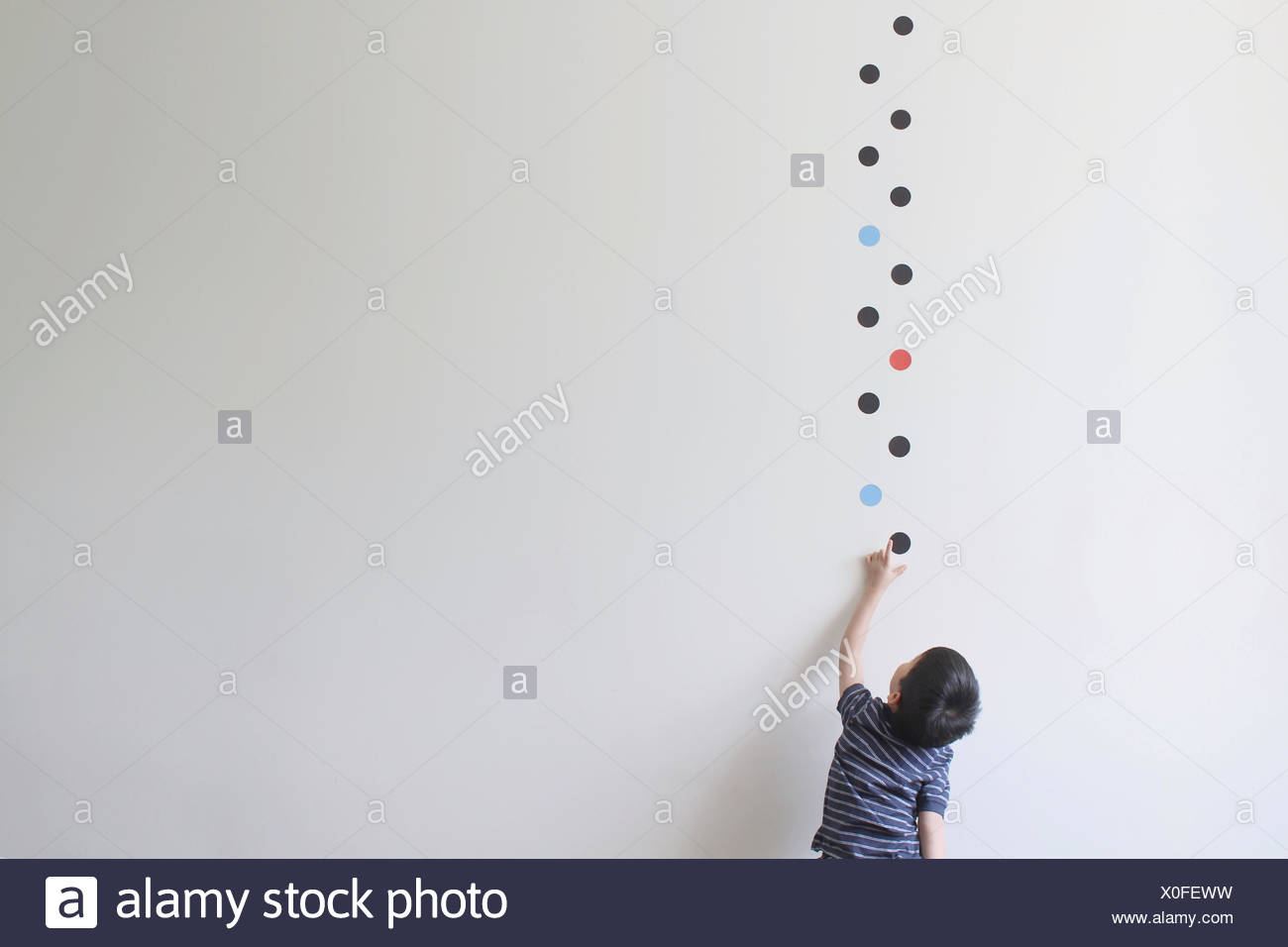 Boy trying to pick one of the dot patterns off the wall - Stock Image