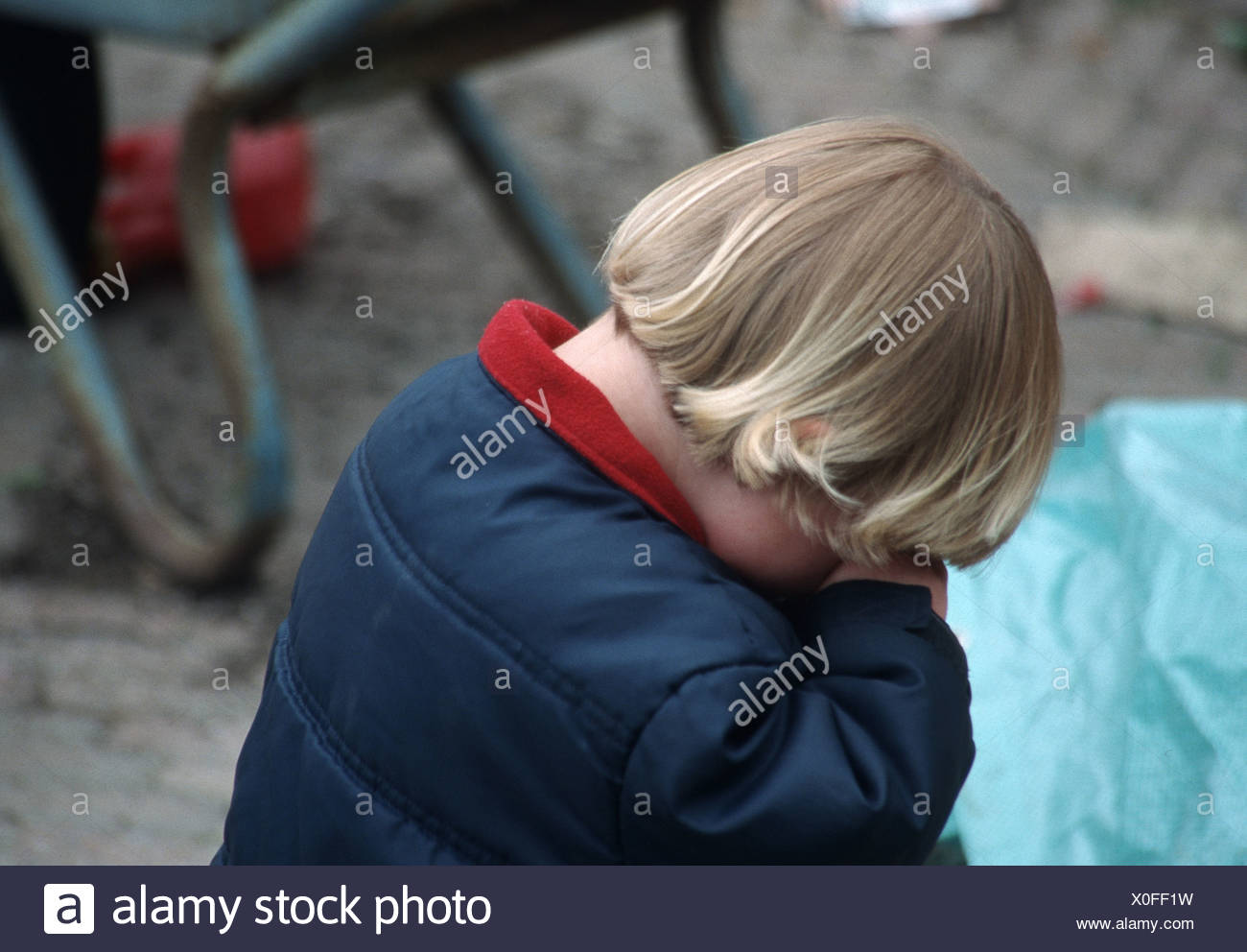 Toddler having a tantrum outside and hiding face and weaning - Stock Image