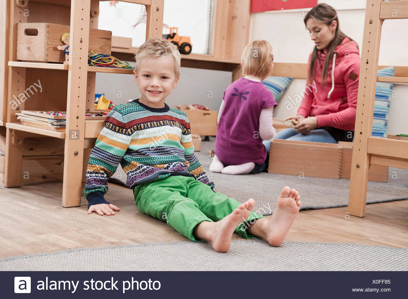 Little boy sitting on the ground in his kindergarten - Stock Image